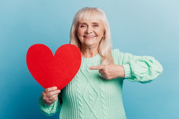 Smiling elderly woman hold point finger red heart card isolated on blue background