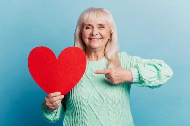 Улыбающаяся пожилая женщина держит указательный палец с красной сердечной картой, изолированной на синем фоне