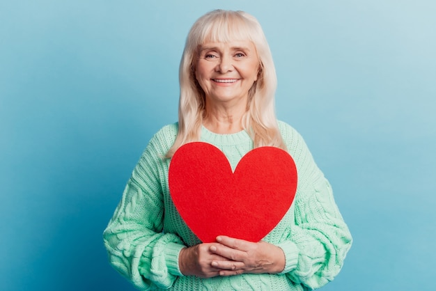 Smiling elderly woman hold red heart card isolated on blue background