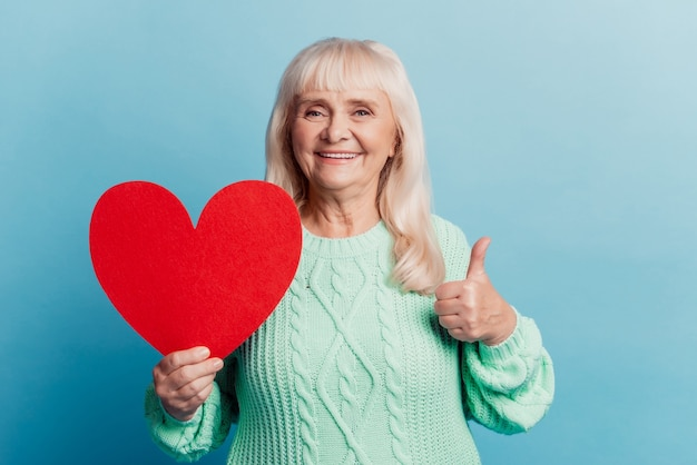 Smiling elderly woman hold red heart card show thumbup fine sign isolated on blue background