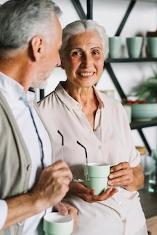 Smiling elderly woman holding cup of coffee standing with her husband