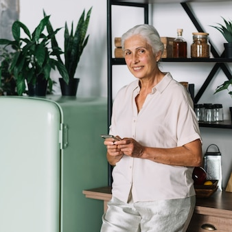 Smiling elderly woman holding mobile standing in front of shelf