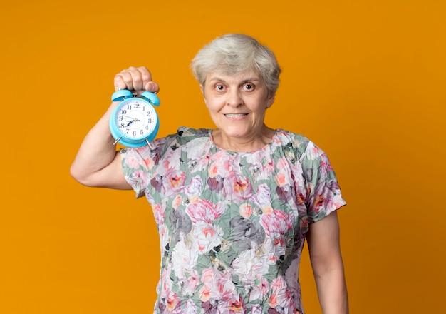 La donna anziana sorridente tiene la sveglia isolata sulla parete arancione