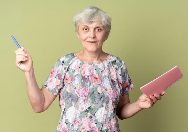 La donna anziana sorridente tiene il taccuino e la penna isolati sulla parete verde oliva