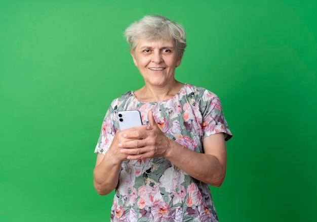 La donna anziana sorridente tiene il telefono isolato sulla parete verde
