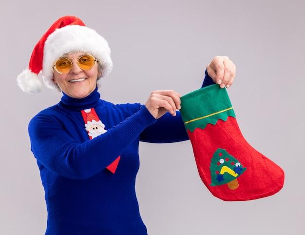 산타 모자와 산타 넥타이와 태양 안경에 웃는 노인 여성 복사 공간이 흰 벽에 고립 된 크리스마스 스타킹을 들고