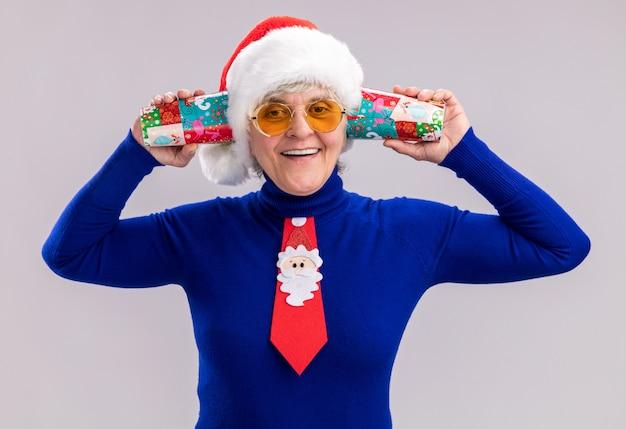 コピースペースと白い背景で隔離の耳の近くに紙コップを保持しているサンタ帽子とサンタネクタイとサングラスで笑顔の年配の女性