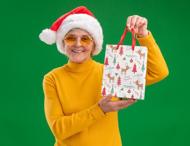 コピースペースで緑の背景に分離された紙のギフトバッグを保持しているサンタ帽子とサングラスで笑顔の年配の女性