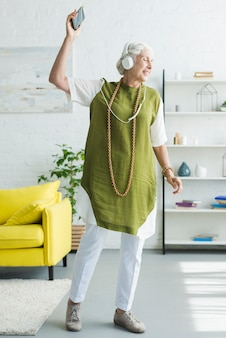 Smiling elderly woman listening music on headphone dancing at home