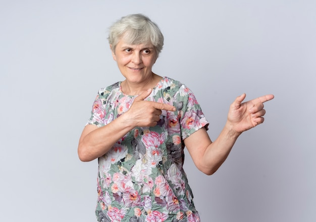La donna anziana sorridente guarda e indica a lato con due mani isolate sulla parete bianca