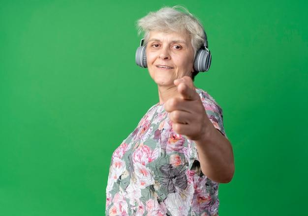 헤드폰 외모와 녹색 벽에 고립 된 포인트에 웃는 노인 여성