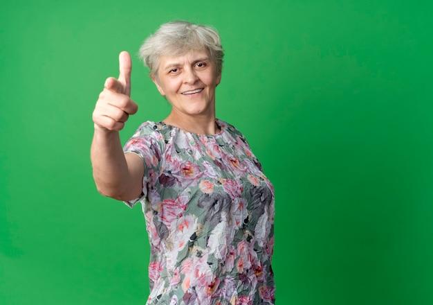 Улыбаясь пожилая женщина указывает на зеленую стену