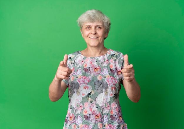 Punti di donna anziana sorridente con due mani isolate sulla parete verde