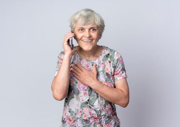 La donna anziana sorridente mette la mano sul mento che parla sul telefono isolato sulla parete bianca