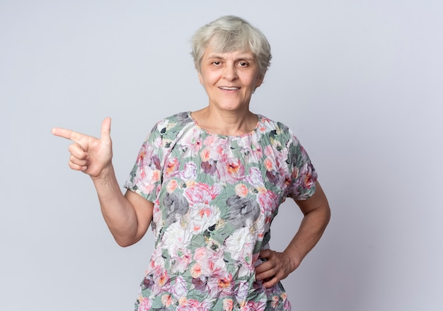 웃는 노인 여성이 흰 벽에 고립 된 측면을 가리키는 허리에 손을 넣습니다.