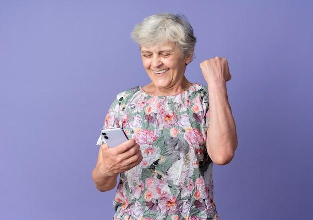 Sorridente donna anziana solleva il pugno guardando il telefono isolato sulla parete viola