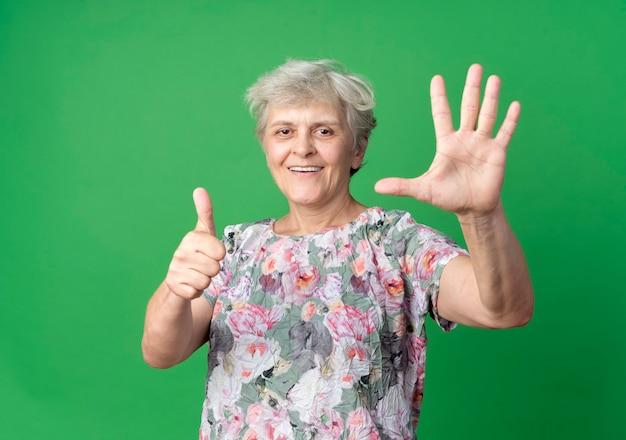 笑顔の年配の女性は、緑の壁で隔離の手と親指を上げます