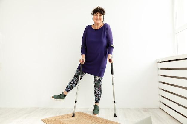 Улыбается пожилая женщина восстанавливается после травмы ноги. стоя на кастах в кабинете физиотерапевта. позитивные эмоции.