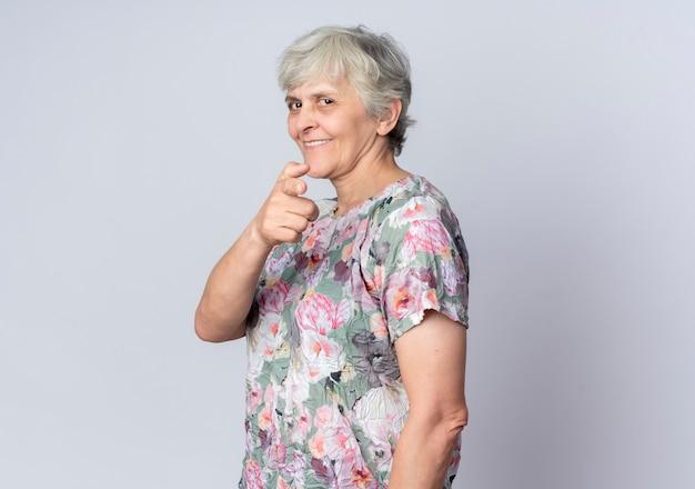 La donna anziana sorridente sta indicando lateralmente isolato sulla parete bianca