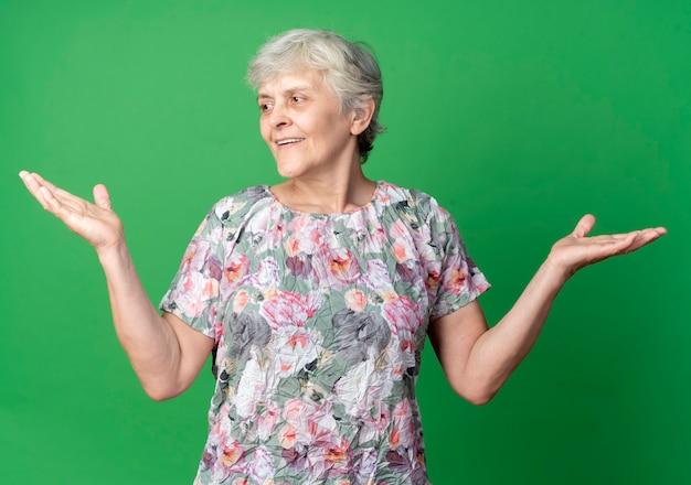 笑顔の年配の女性は、緑の壁に隔離された側を見て手を上げて立っています