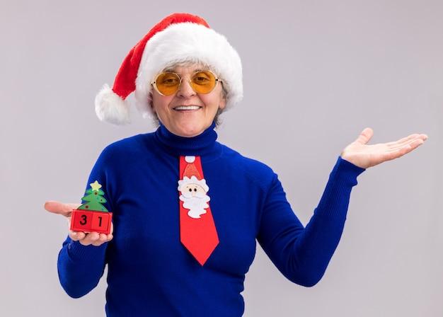 Sorridente donna anziana in occhiali da sole con santa cappello e cravatta santa tenendo l'ornamento dell'albero di natale e tenendo la mano aperta isolato su sfondo bianco con spazio di copia