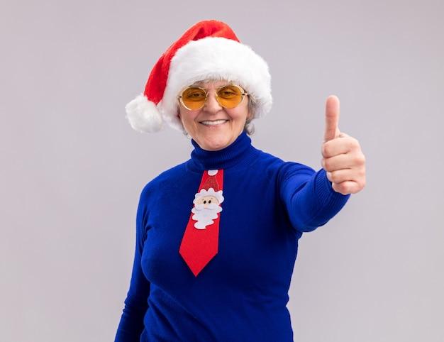 Sorridente donna anziana in occhiali da sole con cappello da babbo natale e santa cravatta pollici in su isolato sul muro bianco con copia spazio