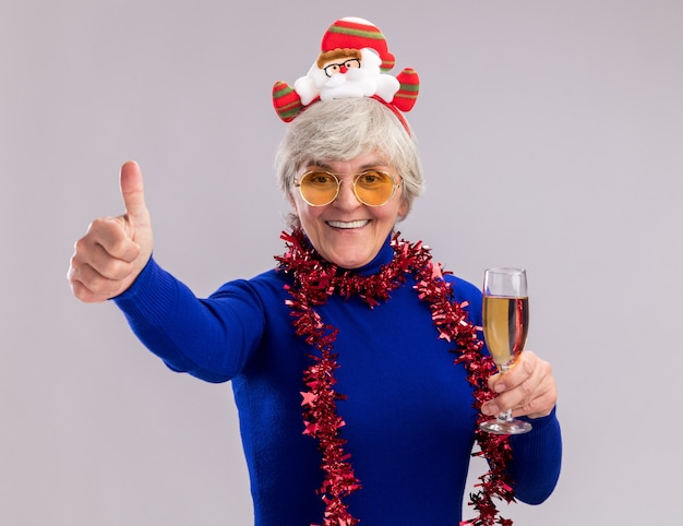 Smiling elderly woman in sun glasses with santa headband and garland around neck holds glass of champagne and thumbs up isolated on white wall with copy space