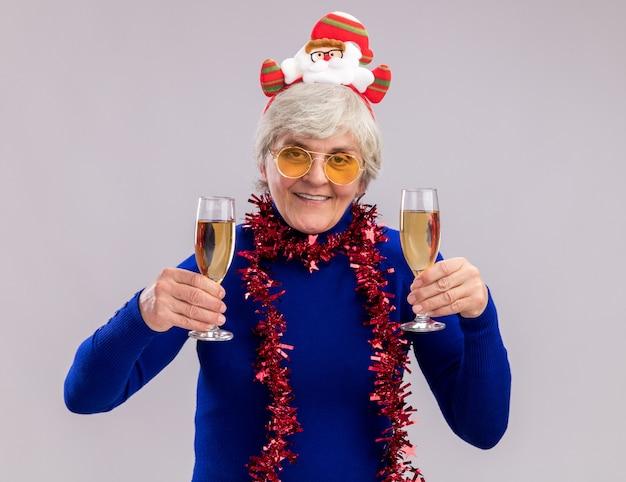 Sorridente donna anziana con occhiali da sole con fascia santa e ghirlanda intorno al collo tiene bicchieri di champagne isolato su sfondo bianco con spazio di copia