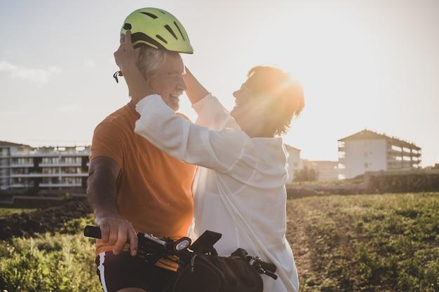 Улыбающаяся пожилая женщина заботится о своем муже-велосипедисте, надевая шлем перед поездкой на велосипеде. яркий закатный свет