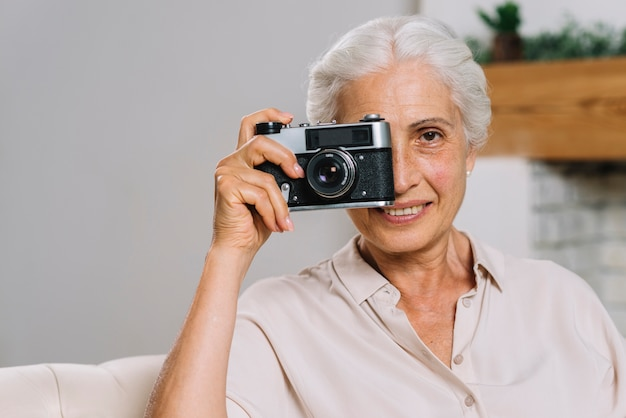 Smiling elderly woman taking photograph from camera