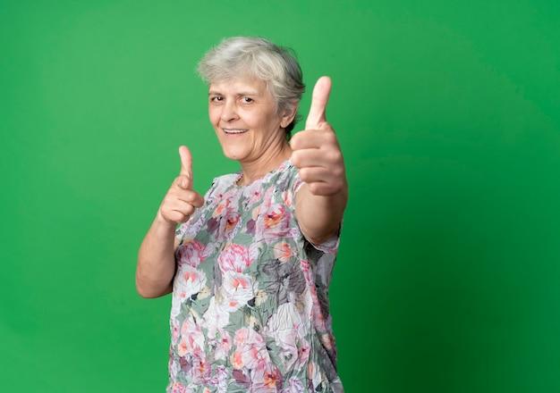 웃는 노인 여성 엄지 손가락 및 녹색 벽에 고립 된 포인트