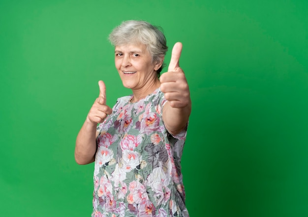 Smiling elderly woman thumbs up and points isolated on green wall