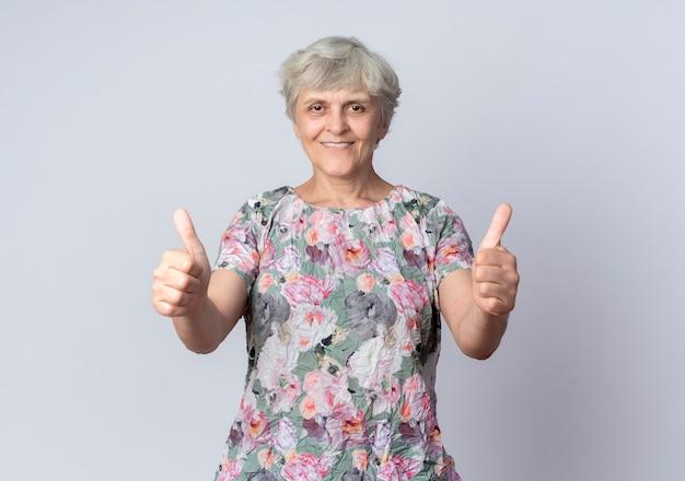 笑顔の年配の女性は白い壁に分離された両手で親指を立てる