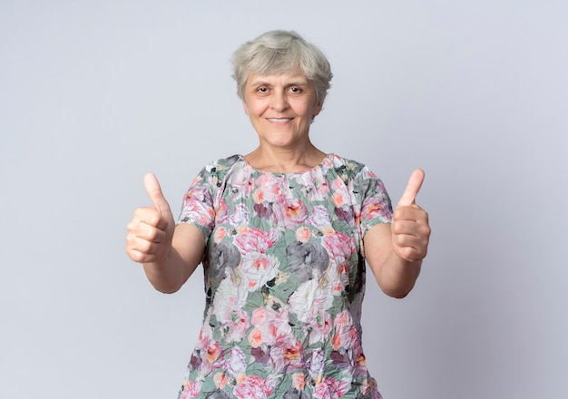 Sorridente donna anziana pollice in alto con due mani isolate sul muro bianco