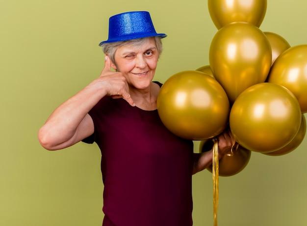 파티 모자를 쓰고 웃는 노인 여성이 헬륨 풍선으로 눈을 깜박입니다.