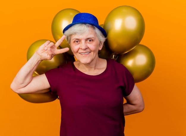 Sorridente donna anziana che indossa il cappello del partito gesti il segno della mano di vittoria e tiene palloncini di elio