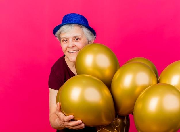 パーティーハットをかぶって笑顔の年配の女性は、ピンクのヘリウム気球を持って立っています
