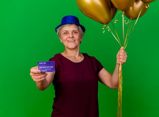 La donna anziana sorridente che porta il cappello del partito tiene la carta di credito e gli aerostati dell'elio sul verde