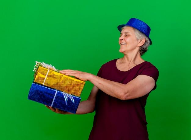 La donna anziana sorridente che porta il cappello del partito tiene i contenitori di regalo che esaminano il lato sul verde