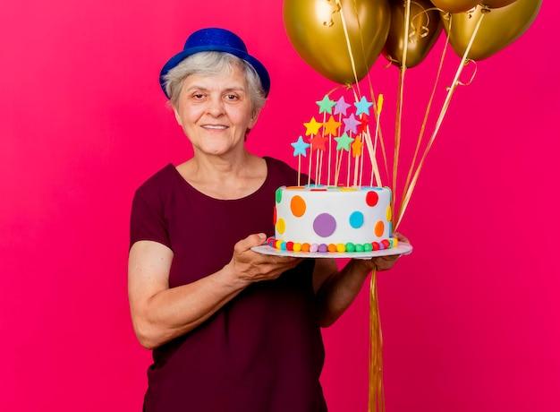 パーティーハットをかぶって笑顔の年配の女性はピンクのカメラを見てヘリウム気球とバースデーケーキを保持します。