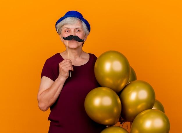 パーティーハットをかぶって笑顔の年配の女性は、オレンジ色の壁に分離された棒にヘリウム気球と偽の口ひげを保持します。