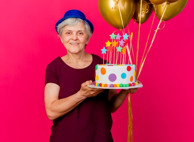 Smiling elderly woman wearing party hat holds helium balloons and birthday cake looking at camera on pink
