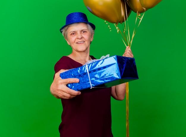 La donna anziana sorridente che porta il cappello del partito tiene i palloni dell'elio e la confezione regalo sul verde