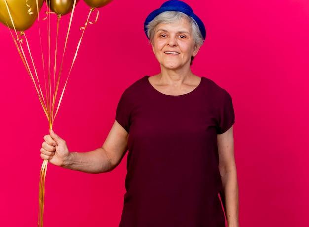 パーティーハットをかぶって笑顔の年配の女性はピンクのヘリウム風船を保持