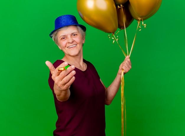 La donna anziana sorridente che porta il cappello del partito tiene i palloni dell'elio e il fischio sul verde