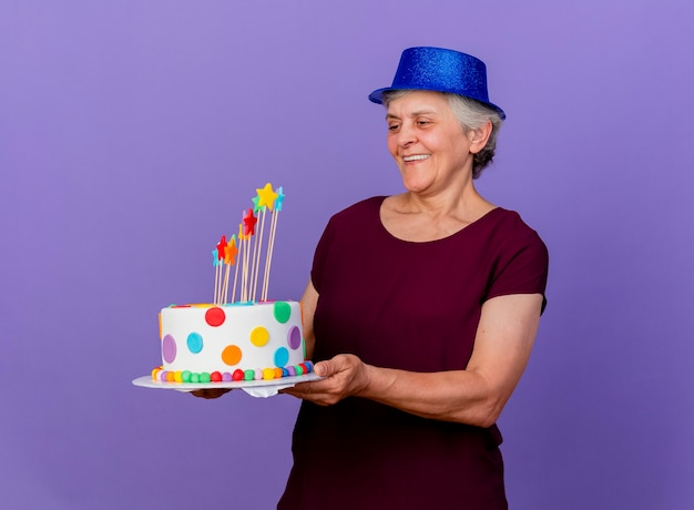 Smiling elderly woman wearing party hat holds and looks at birthday cake isolated on purple wall with copy space