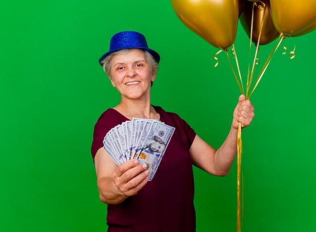 La donna anziana sorridente che porta il cappello del partito tiene i palloni dell'elio e dei soldi sul verde