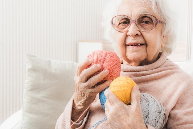 Улыбающаяся пожилая женщина, держащая разноцветные кружева