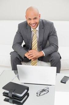 Smiling elegant businessman with laptop at home