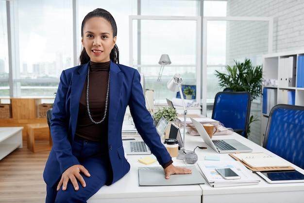 彼女のオフィスの机に寄りかかってカメラを見て青いスーツを着たエレガントな実業家の笑顔